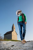 Posing young woman in a stylish hat and an old romanesque church. Archangel Michael in Slovak republic Stock Photography