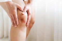 Posiniaczony kolano Asia kobieta, selekcyjna ostrość fotografia royalty free