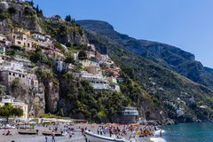 Positano, Amalfi Coast, Italy - April 9, 2017: many people rest on the coast in the background of mountains with traditional Itali royalty free stock photography