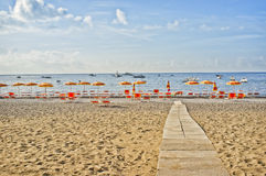 Positano Beach, Amalfi Coast,  Italy. The pebble and sand beach with orange umbrellas and chairs, at the village of Positano, in southern Italy, on the Royalty Free Stock Photos