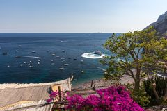 Positano framed by pink bougainvillea and boats in the background. Colourful Positano, the jewel of the Amalfi Coast, Stock Photo