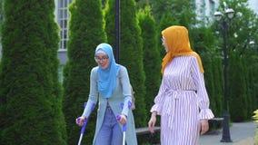 Positief die jonge vrouw in hijab op steunpilaren na verwonding met meisje het lopen in Park glimlachen stock videobeelden