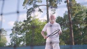 Positief die rijp mensen speeltennis op de tennisbaan glimlachen De oude man werpt de bal met de racket actief stock videobeelden