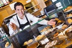 Positief glimlachend koffiepersoneel die luim en biscuitgebak aanbieden royalty-vrije stock afbeelding