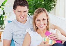 Positief glimlachend paar met vrouwen openingsheden stock fotografie