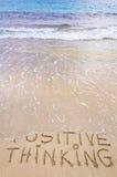 Positief het Denken bericht dat op zand, met golven op achtergrond wordt geschreven Stock Afbeeldingen