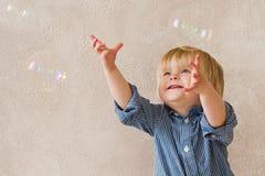 Positief jong geitje die zeepbels vangen Stock Fotografie