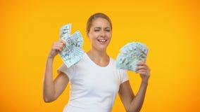 Positief jong wijfje die met in hand dollars dansen, rijkdomopwinding, loterij stock footage