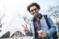 Positief knap donker-gevild mannetje met afrokapsel die vrede of overwinningsgebaar tonen terwijl het wandelen over stad royalty-vrije stock afbeeldingen