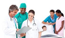 Positief medisch team dat een kleine jongen behandelt Stock Foto's