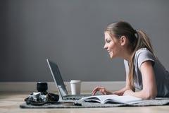 Positief meisje die met laptop Internet surfen, die op de vloer leggen stock foto's