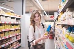 Positief meisje die zich in een supermarkt met een pak graangewassen in haar hand bevinden en de camera onderzoeken stock fotografie