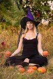 Positief meisje in heksenkostuum het praktizeren yoga Stock Afbeeldingen