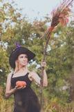 Positief meisje in heksenkostuum met bezemsteel Stock Fotografie