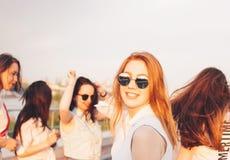 Positief mooi gelukkig rood haired meisje in de spiegelzonnebril met vrienden op blauwe hemelachtergrond, de tijd van de de zomer stock foto's