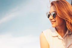 Positief mooi gelukkig rood haired meisje in de spiegelzonnebril op blauwe hemelachtergrond, de tijd van de de zomerzonsondergang stock foto's