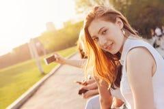 Positief mooi gelukkig rood haired meisje met vrienden op de achtergrond van de stadsstraat, de tijd van de de zomerzonsondergang stock afbeeldingen