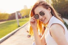 Positief mooi gelukkig rood haired meisje in spiegelzonnebril met vrienden op de achtergrond van de stadsstraat, de tijd van de d royalty-vrije stock fotografie