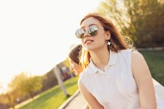 Positief mooi gelukkig rood haired meisje in spiegelzonnebril met vrienden op de achtergrond van de stadsstraat, de tijd van de d royalty-vrije stock foto's