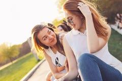 Positief mooi gelukkig rood haired meisje in spiegelzonnebril met vrienden op de achtergrond van de stadsstraat, de tijd van de d stock fotografie