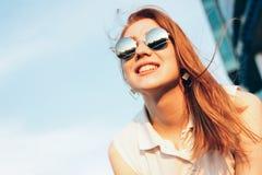 Positief mooi gelukkig rood haired meisje in spiegelzonnebril op blauwe hemelachtergrond, de tijd van de de zomerzonsondergang stock fotografie