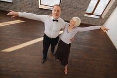 Positief oud danspaar die in de dansstudio walsen stock foto's