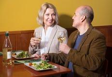 Positief rijp paar die diner hebben bij restaurant stock foto