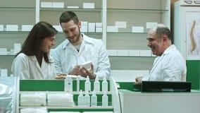 Positief team van apothekers die doos van tablet bij de het ziekenhuisapotheek bekijken stock video
