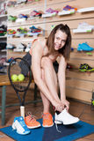 Positief tienermeisje die professionele tennisschoenen proberen Stock Afbeelding