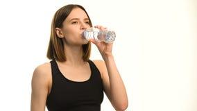 Positief vrouwelijk geschiktheidsmodel na training drinkwater in studio over witte achtergrond stock videobeelden