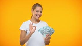 Positief wijfje die de o.k. in hand dollars van de gebaarholding, financiële investering tonen stock video
