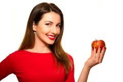 Positief Wijfje die een Groot Rood Apple-Fruit bijten die op Witte Bedelaars glimlachen Royalty-vrije Stock Afbeeldingen