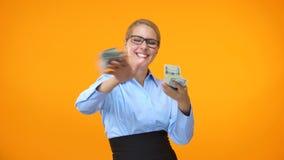 Positief wijfje die in formeel kostuum dollars werpen rond, financiële onafhankelijkheid stock video