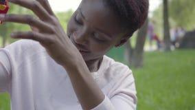 Positieve Afrikaanse Amerikaanse vrouw die met haar weinig zoon spelen die plastic stuk speelgoed in het park gebruiken Het jonge stock footage