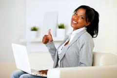Positieve Afro-Amerikaanse jonge vrouw die aan u kijkt Stock Foto
