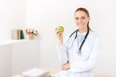 Positieve arts die groene appel houden Royalty-vrije Stock Foto's