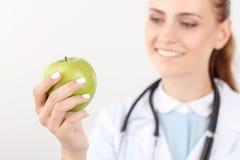 Positieve arts die groene appel houden Stock Foto