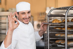Positieve bakker die vers gebakken brood controleren stock fotografie