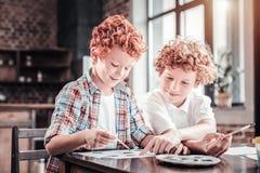 Positieve begaafde jongens die een beeld schilderen Stock Afbeelding