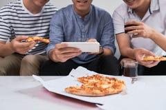 Positieve blije vrienden die van hun pizza genieten royalty-vrije stock foto