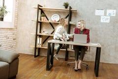 Positieve blondevrouw die in rood jasje aan haar luide dochter luisteren stock foto's
