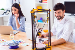 Positieve collega's die 3d printer met behulp van Stock Foto