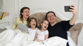 Positieve Familie Selfie met Moeder, Vader en Twee Kinderen die op het Bed liggen en Pyjama's dragen De knappe Mens neemt stock footage