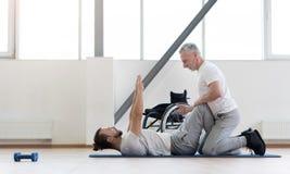 Positieve fysiotherapeut die de gehandicapten bijstaan in de gymnastiek stock foto