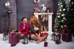 Positieve gebaarde echtgenoot die zijn charmante vrouw onderhouden tijdens Nieuwjaarvakantie royalty-vrije stock afbeelding