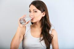 Positieve gelukkige glimlachende vrouw die met gezonde huid en lang krullend haar zuiver water en het kijken drinken close-up royalty-vrije stock foto