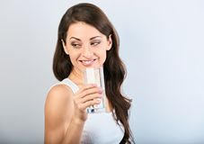 Positieve gelukkige glimlachende vrouw met gezonde huid en lang krullend haar die zuiver water drinken en terug op blauwe achterg stock foto's