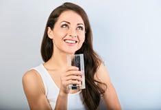 Positieve gelukkige glimlachende vrouw met gezonde zuiver water drinken en huid en lang krullend haar die omhoog eruit zien stock foto's
