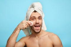 Positieve gelukkige mens die poeder op zijn gezicht toepassen royalty-vrije stock foto