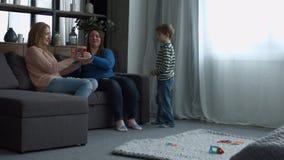 Positieve glimlachende vrouwen die met kind thuis spelen stock videobeelden